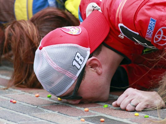 Kyle Busch kisses the bricks on the start/finish line after winning Sunday's Brickyard 400 at Indianapolis Motor Speedway in Indianapolis.