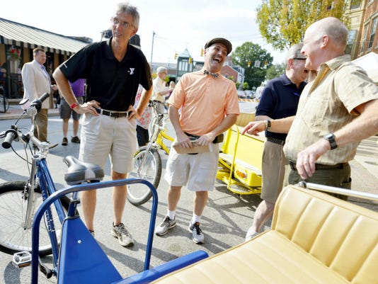 i-ron-ic co-owner and Pedi Cabs of York driver Steve Billet, second from left, shares a laugh with York YMCA executive director Craig Wolf, far left, York City Council member Henry Nixon and Downtown Inc. project coordinator Tim Fulton on Friday, Aug. 7, 2015, on North Beaver Street during First Friday festivities. Pedi Cabs of York, dreamed up by i-ron-ic art gallery and thrift store owners David Smith and Steve Billet, will provide free, human-powered rides around York City's central business district.