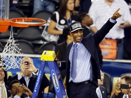 Connecticut head coach Kevin Ollie celebrates while cutting down the net after beating Kentucky 60-54, at the NCAA Final Four tournament college basketball championship game Monday, April 7, 2014, in Arlington, Texas. (AP Photo/Tony Gutierrez)