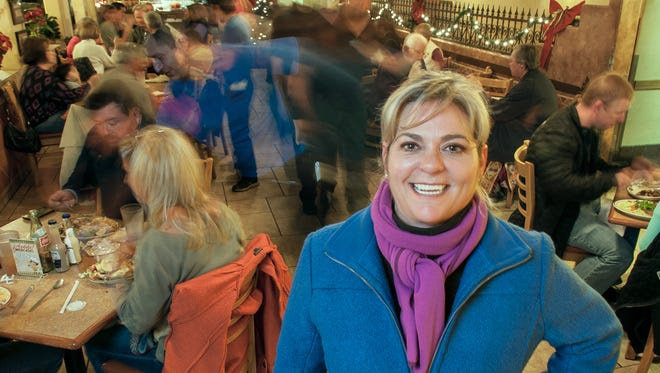 Andrea Schneider, owner of Andele Restaurant, poses for a photograph on a busy night in her restaurant.