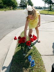 Miller Rose Mozingo, the youngest daughter of Circuit Judge Tony Mozingo, adjusts a bouquet of Mother's Day roses that the family placed near the site where two Hattiesburg, Miss., police were fatally shot the night before, Sunday, May 10, 2015, in Hattiesburg. Three suspects were in custody, including two who are charged with capital murder.