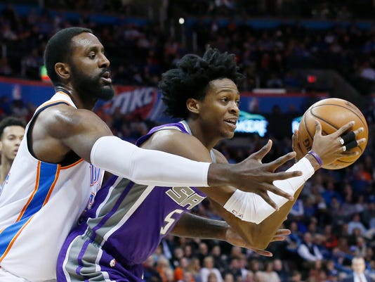 Sacramento Kings guard De'Aaron Fox, right, keeps the ball away from Oklahoma City Thunder forward Patrick Patterson, left, in the second quarter of an NBA basketball game in Oklahoma City, Monday, Jan. 15, 2018. (AP Photo/Sue Ogrocki)