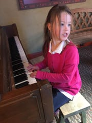 Clara Cater, 6, plays the piano during a recent visit to cMoe.