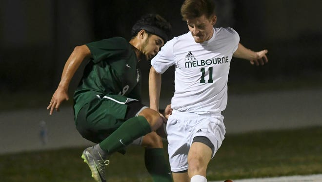 Melbourne's Kai Rittgers (11) and Alex Cruz of Fleming Island contend for the ball during Friday's Class 4A state soccer semifinal.