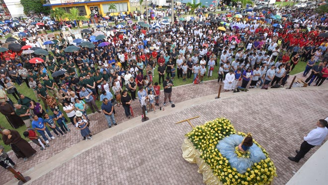 Catholic faithfuls face toward the Santa Marian Kamalen, or Our Lady of Camarin, statue as they pray on the lawn of the Dulce Nombre de Maria Cathedral-Basilica  in Hagåtña, during the celebration of the Immaculate Conception of the Blessed Virgin Mary on Thursday, Dec. 8, 2016.