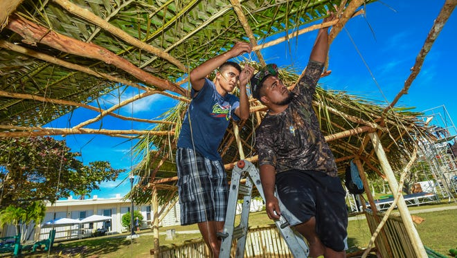 Students Elias David, left, and McHiver Williams add on woven palm fronds to the Kosrae Student Organization's thatched-roof hut they were constructing at the University of Guam during the 2017 CHarter Day celebration.