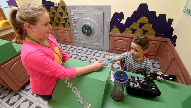 Jayden Lerner, 6 years old, and Faith Dyer, 10 years old, both of Mansfield, Play in the Lil Bank on Saturday morning. The exhibit will be scaled down, and a police and fire exhibit will be added.