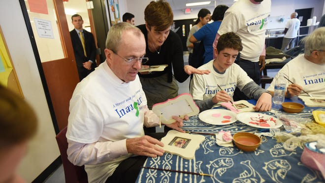 Governor-elect Phil Murphy and his son Sam (age 14) work on painting wooden frames during the MLK Day of Service Project at HomeFront Family Campus in Ewing on 01/15/18.