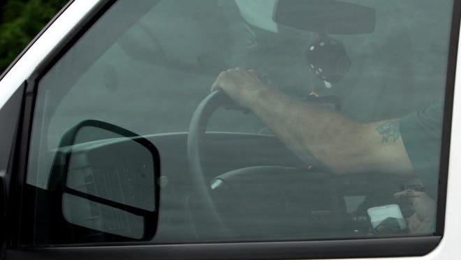 A motorist is seen using a cell phone while driving along Route 684 in Somers July 25, 2013 during an earlier state police enforcement action
