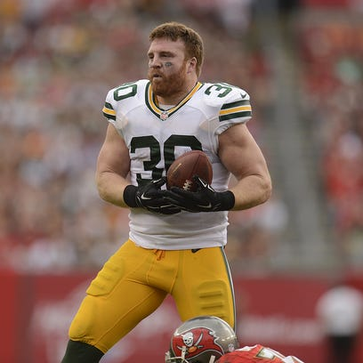 Packers fullback John Kuhn loses his helmet after being