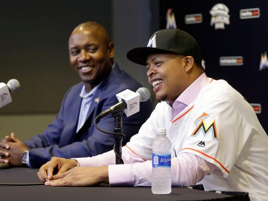 Right-hander Edinson Volquez, right, smiles as he talks to reporters as Miami Marlins general manager Michael Hill, left, looks on during a news conference at Marlins Park, Thursday, Dec. 1, 2016, in Miami. Volquez has finalized a $22 million, two-year contract with the Miami Marlins. He joins a rotation shaken by the loss of ace Jose Fernandez, who died in a boating accident a week before the end of the regular season in September. (AP Photo/Alan Diaz)