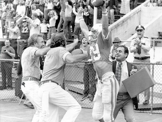 Tennessee wide receiver Larry Seivers is greeted in the end zone by a pair of zealous fans as well as a cigar-smoking, briefcase-toting Gus Manning after catching a two-point conversion pass from Condredge Holloway against Clemson on Oct. 26, 1974, at Neyland Stadium to help the Vols down the Tigers 29-28.