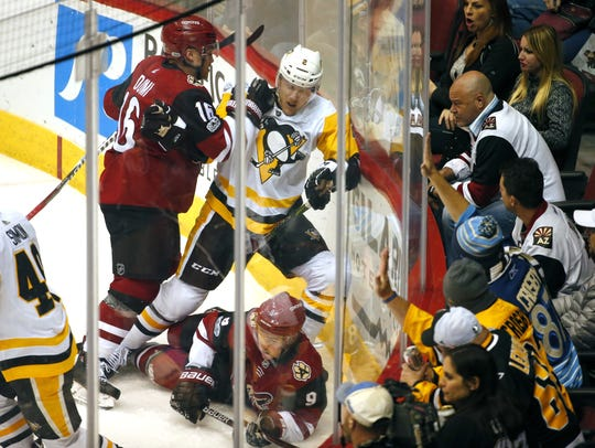 Coyotes left wing Max Domi (16) and Penguins defenseman Chad Ruhwedel (2) fight during Saturday's game.