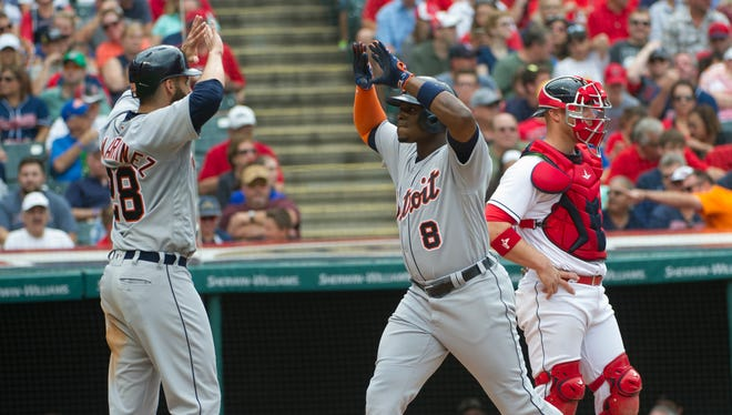 Tigers' Justin Upton (8) is greeted by J.D. Martinez after hitting a two-run homer off Trevor Bauer during the fifth inning in Cleveland, Sunday, Sept. 18, 2016. Indians catcher Chris Gimenez stands in the background.