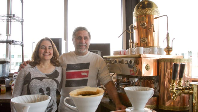 Spouses Janet and Frank DiPiazza, co-owners of the Proper Cup Coffee Shop, stand next to a refurbished 1930s expresso machine in the newly opened venue in Genoa Township.