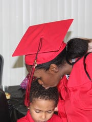 Graduate ShaKeyah Green kisses her son Aiden during
