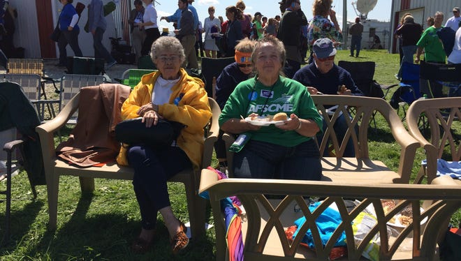 Evelyn West and Della Mull share bench seating at the Harkin Steak Fry on September 14, 2014. Mull drove five benches from Vinton so she could provide seating for other attendees.