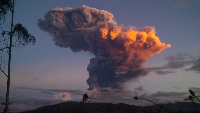 The Tungurahua volcano spews a column of ash as seen from Ambato, Ecuador, Friday, April 4, 2014.