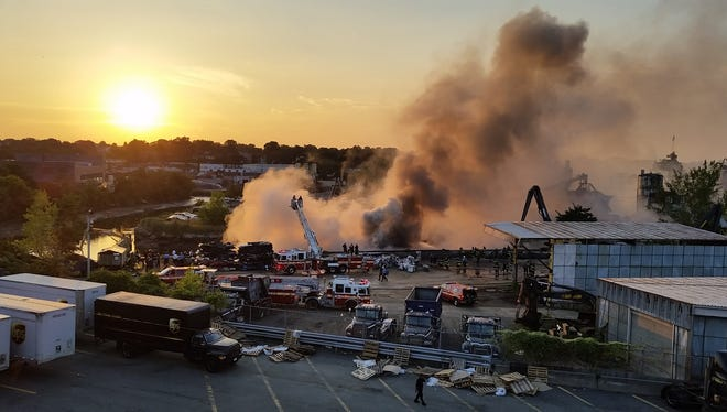 Emergency responders work to contain a fire burning aboard a barge in the Hutchinson River. The barge appeared to contain junked cars and seems to be sitting on the Bronx side of the border with Westchester.