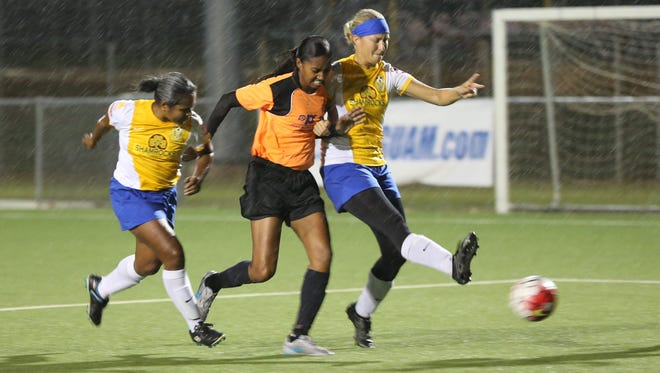 Lady Rovers' Maggie Phillips kicks the ball away from Personal Finance Center Lady Crushers' Simie Willter on her way to the goal, with the Lady Rovers' Blanda Camacho supporting Phillips on defense during an opening week match of the 2016 Bud Light Women's Soccer League Spring season at the Guam Football Association National Training Center. The Lady Crushers won 4-3.