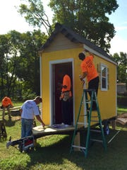 A crew of construction workers put the finishing touches on a colorful collection of micro homes built to help house Nashville homeless.