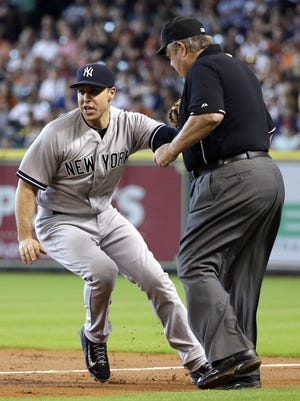 Yankees' Mark Teixeira, left, tries to avoid first base umpire Joe West while fielding a ground ball hit by Houston Astros' Evan Gattis during the second inning of Sunday's game. Gattis was out at first on the play.