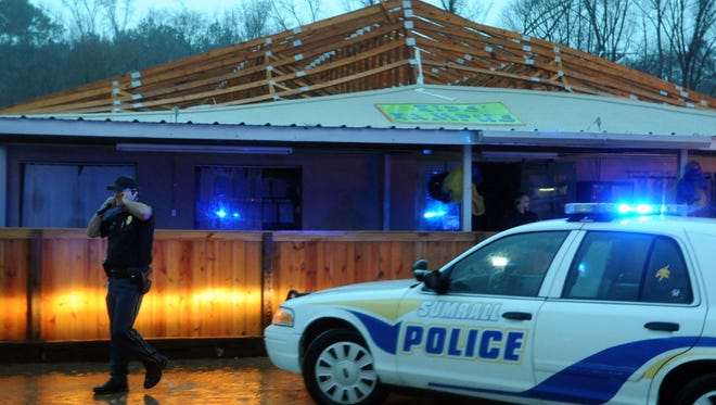 Sumrall Police officers inspect the Kids Kampus day care center in Sumrall after the building sustained heavy tornado damage. According to the Sumrall Police Department, all 30 children and day care employees were unharmed and moved to the neighboring Citizens Bank.