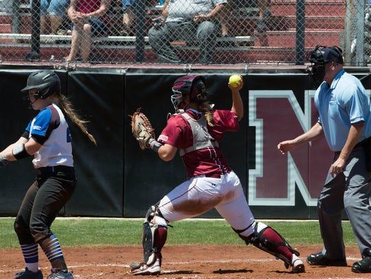 Niki Butler, throws to first base to check a runner
