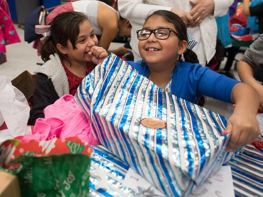 Kanla Galavis unwraps a present during Crockett Elementary's second annual Christmas Tree Angel event on Wednesday, Dec. 13, 2017.