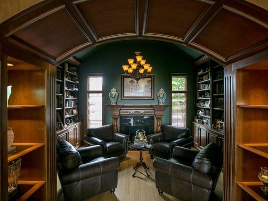 The library is seen through an archway incorporating shelving with a fireplace and bamboo flooring.