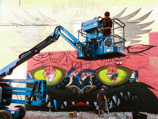 Artist Jeff Soto (bottom) works on the lower half of a mural he teamed up with Maxx242 to paint off of Gratiot during the Murals in the Market festival on Friday, Sept. 18, 2015, at the Eastern Market in Detroit.