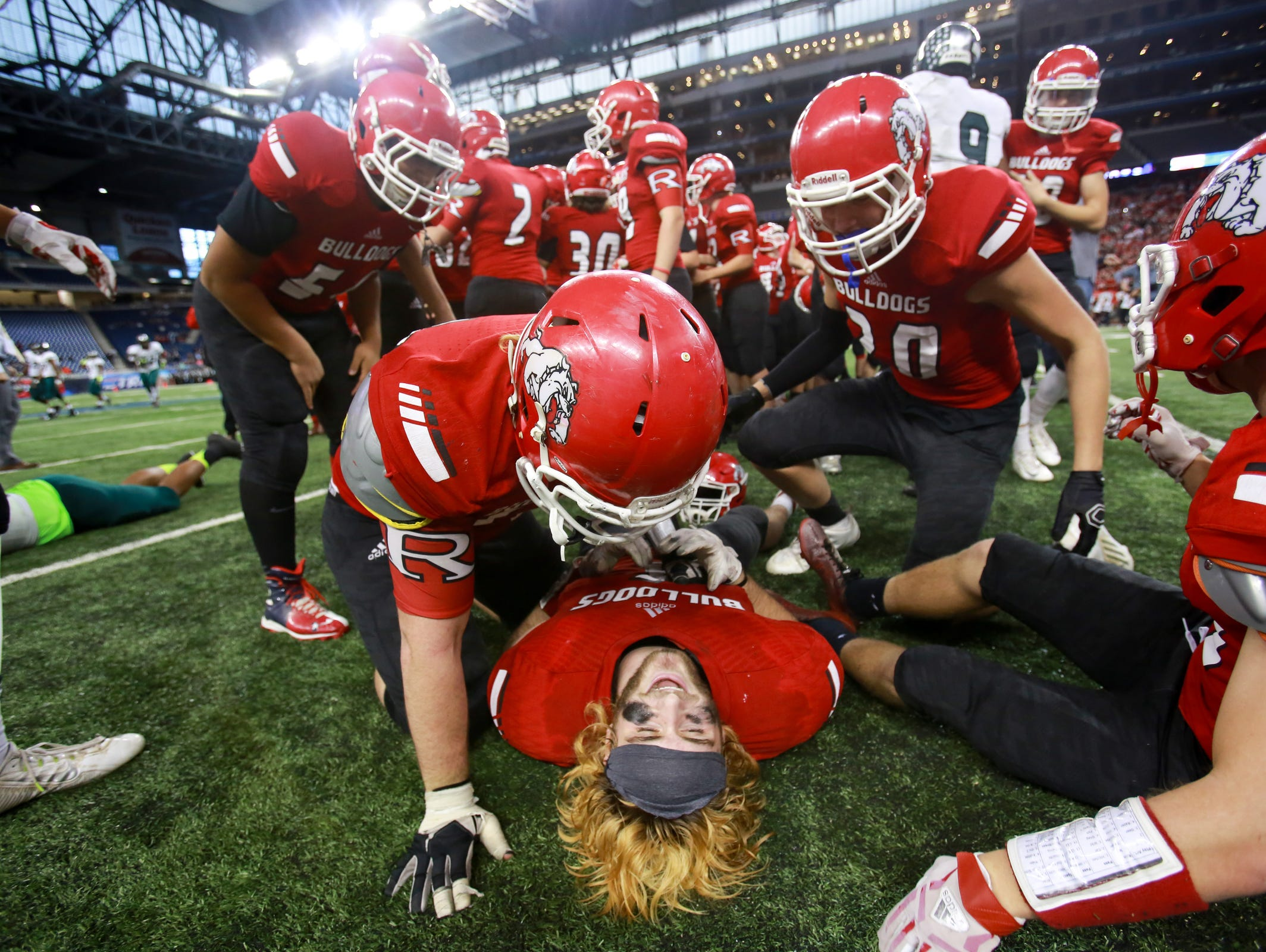 Romeo TE Mitchell Heimbuch is surrounded by his teammates after they defeated Detroit Cass Tech 41-27, during the Michigan High School Athletic Association football Division 1 finals at Ford Field in Detroit on Saturday, Nov. 28, 2015.