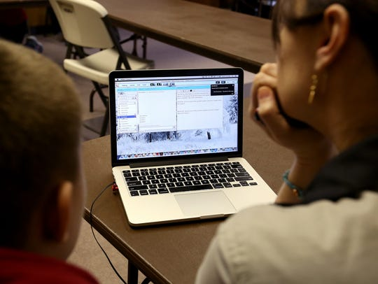 A teacher works with students in a virtual classroom