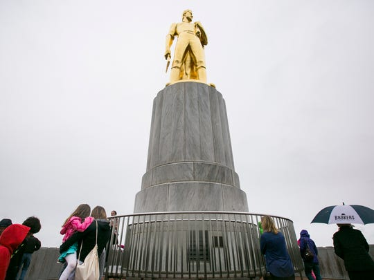 Visitors stand on the rooftop platform of the Capitol and gaze up at the Oregon Pioneer statue in the rain on Monday, March 21, 2016. Weather permitting, tower tours are run four times a day during spring break. The Capitol also runs four building tours a day, rain or shine, that visit the rotunda, the legislative chambers and the governor's ceremonial office.