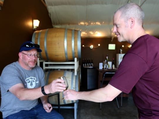Mike Hinds, right, gives Eric Eckfield of Salem a tasting at Hanson Vineyards outside Woodburn in 2016.