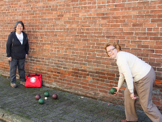 Laurie Naemura and Suzie Hubert from the Salem Bocce League demonstrate how to play bocce at Holding Court.