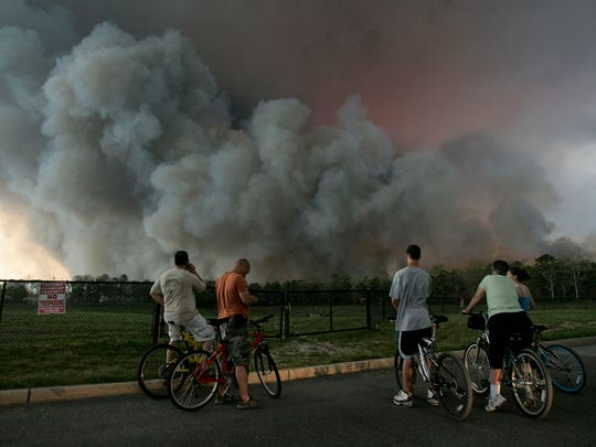 Cyclists stop on Neptune Drive to look at a large cloud of smoke rising over Rt 72 late Tuesday afternoon, May 16, 2007.