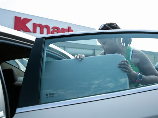 Kenya Travis of Madison Heights loads a folding table in her car after buying it from Kmart in Warren in 2017.