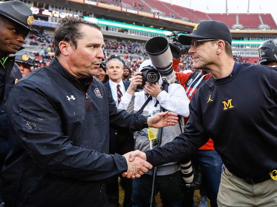 Michigan coach Jim Harbaugh shakes hands with South Carolina coach Will Muschamp after the Wolverines' 26-19 loss in the Outback Bowl at Raymond James Stadium in Tampa, Fla., Monday, Jan. 1, 2018.
