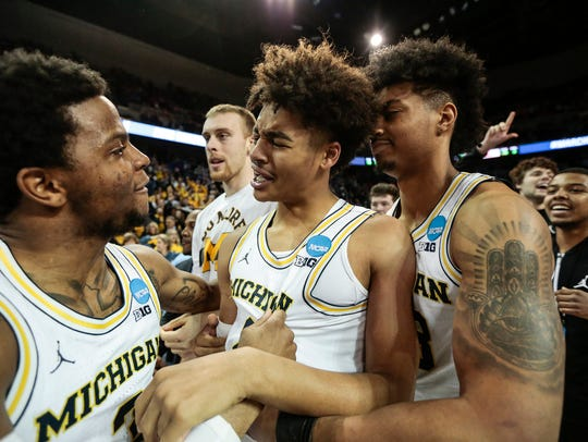 Michigan's Jordan Poole, center, celebrates his buzzer-beater