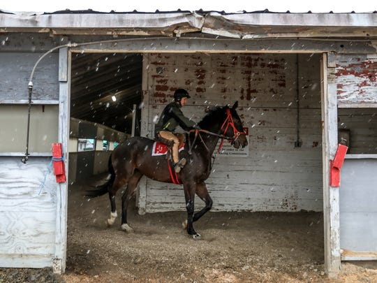 Jockey Melissa Zajac, 31,  works out a horse by taking laps in an abandoned stable at Hazel Park Raceway on Wednesday, April 11, 2018, after the track was closed. Zajac plans to continue racing horses in Cincinnati, Ohio.
