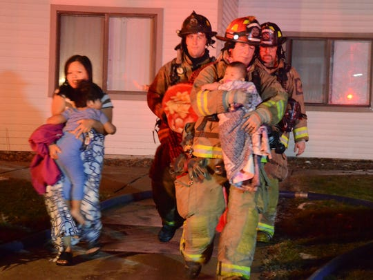 Firefighters assist a family from one of the apartments.