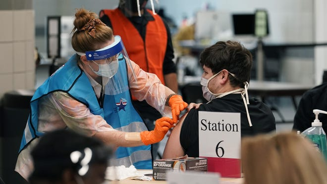 A health care worker administers a vaccination at the new Alamodome COVID-19 vaccine site Monday in San Antonio, Texas. Officials say the site is providing 1,500 vaccinations per day.