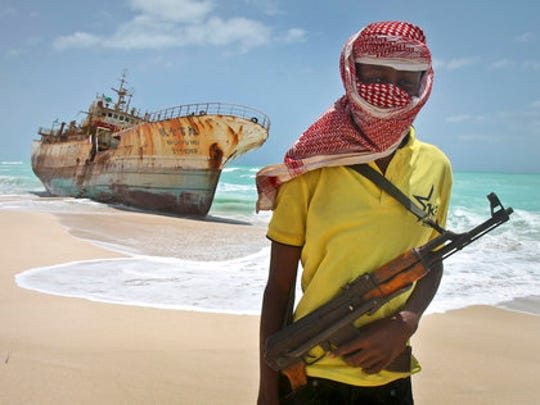 FILE - In this Sunday, Sept. 23, 2012 file photo, masked and armed Somali pirate Hassan stands near a Taiwanese fishing vessel washed ashore after the pirates were paid a ransom and the crew were released in the once-bustling pirate den of Hobyo, Somalia. Pirates have hijacked an oil tanker off the coast of Somalia, Somali officials and piracy experts said Tuesday, March 14, 2017, in the first hijacking of a large commercial vessel there since 2012.