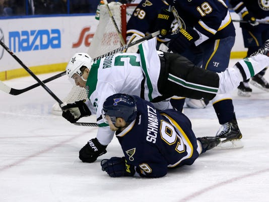 Dallas Stars' Antoine Roussel falls over St. Louis Blues' Jaden Schwartz while chasing the puck during the first period of an NHL hockey game Saturday, March 29, 2014, in St. Louis. (AP Photo/Jeff Roberson)