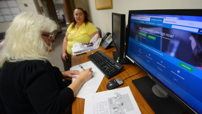 Application counselor Shawn Powell, left, assists Donna Kiernan of Green Bay with her health care application process at St. Vincent Hospital. Kiernan previously was unable to afford health insurance.