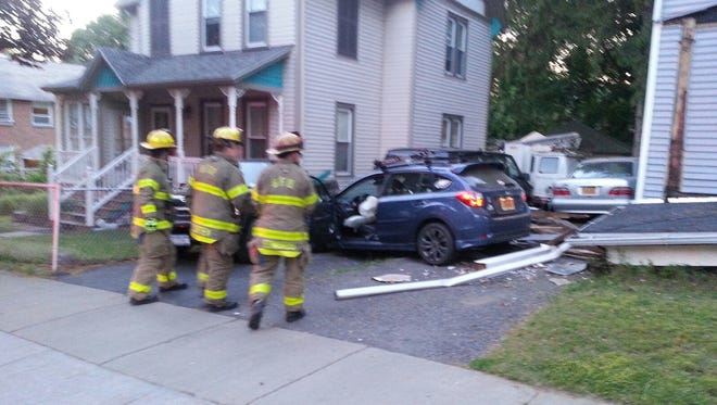Firefighters at the scene Thursday morning after a stolen vehicle crashed into the porch of a Mitchell Avenue home in Binghamton.