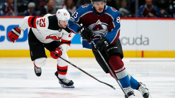 Colorado Avalanche left wing Matt Nieto, front, picks up a loose puck in front of New Jersey Devils right wing Stefan Noesen during the third period of an NHL hockey game Friday, Dec. 1, 2017, in Denver. The Devils won 2-1. (AP Photo/David Zalubowski)