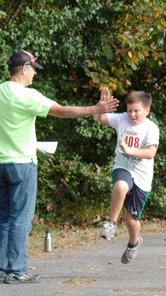Runner Matthew Cabrera rounds the track at Glen Marlow Elementary School as he 'high fives' race official Tom Sharkey. He competed in the Healthy Kids Running Series in the 1-mile distance with other fourth and fifth graders.