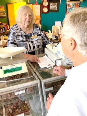 Marjorie Hamminga, owner of The Tasty Nut Shop in White Pigeon, assists Leroy Chupp at an open house Saturday to mark the 100th anniversary of the business.